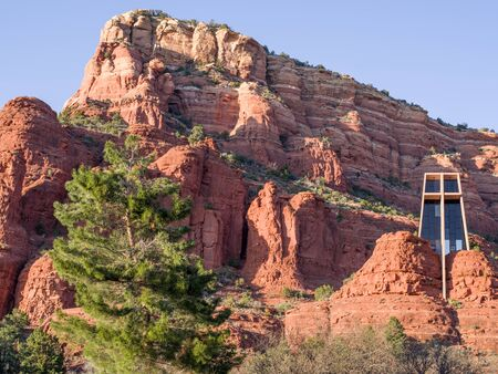 Red rock massive with Chapel of the Holy Cross near Sedona seen in a bright spring sunny afternoon with a large pine tree in foreground Фото со стока