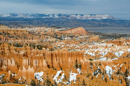 Sun lit Bryce Canyon in detailed (still broad) view. Red  ochre canyon rock formations in places overgrown by green pines, partly covered by white snow. Mountains on distant horizon