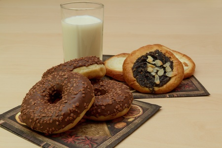 Cheese and poppy cake and chocolate donuts with a glass of milk
