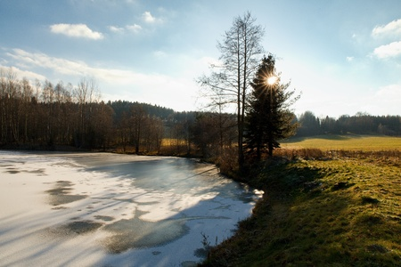 View of landscape with pond and meadow at sunset in Rumburk, Czech Republic Stock Photo