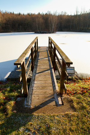 View of the winter landscape with a footbridge to the pond with an island Stock Photo