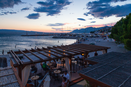 Baska Voda, Croatia, July 23, 2018: View of the beach and restaurant in Baska Voda and the Biokovo Mountains in the background in Croatia