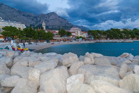 Baska Voda, Croatia, July 23, 2018: View of the beach in Baska Voda and the Biokovo Mountains in the background in Croatia