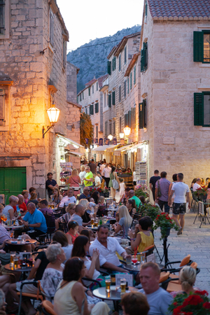 Omis, Croatia, July 19, 2018: Street with people and cafes at old city center in Omis, Dalmatia, Croatia