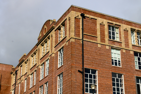 The red brick and yellow stone facade of an old cotton mill 版權商用圖片 - 90657238