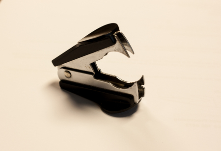 A staple extractor sits on top of a white piece of paper Stock Photo