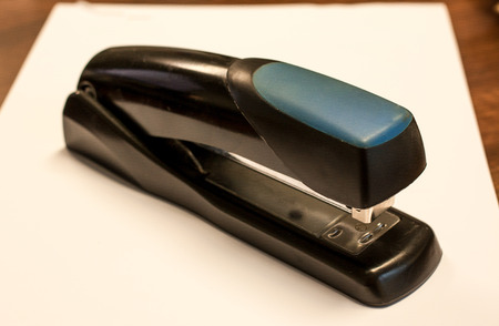 A stapler sits on top of a white sheet of paper Stock Photo
