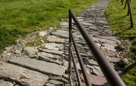 The open metal gate leading on to a cobbled stone path Stock Photo