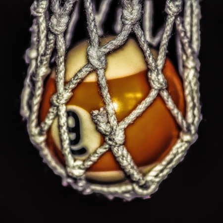 A yellow and white pool ball in a string pocket