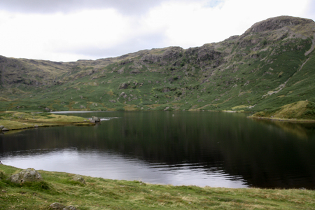 The still and calm waters of Easedale Tarn in the Lake District National Park