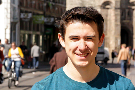 A young man smiles in the street in Europe Stock fotó