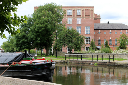 A view of years gone by with a canal barge moored up outside an old cotton mill on the Leeds Liverpool canal