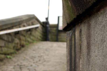 Peeping around the corner of a stone and concrete wall towards a cobbled path and handrail