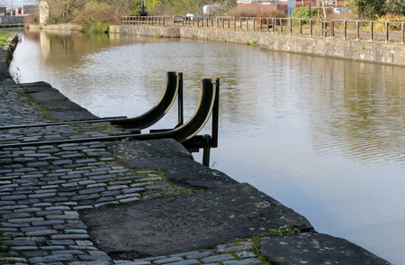 The short and historic Wigan Pier next to the cobbled towpath that runs alongside it on the Leeds Liverpool canal