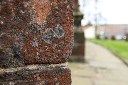 Peering around the edge of the red stone architecture of a church in Standish, Wigan Stock Photo