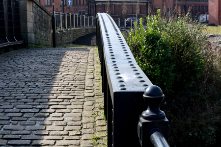 The riveted black iron bridge over the canal with the cobbles Stock Photo