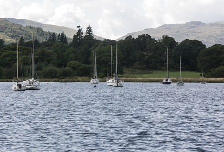 The waters of Windermere with sailing boats and a forest in the background