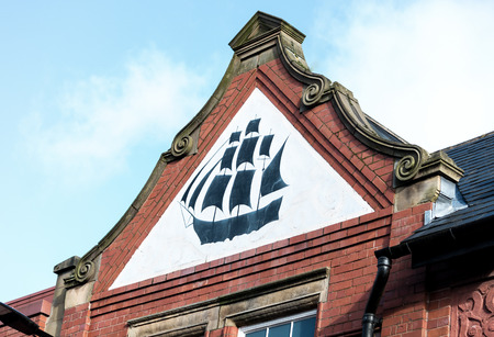 A red brick building with the apex showing a black ship on white background Stock Photo