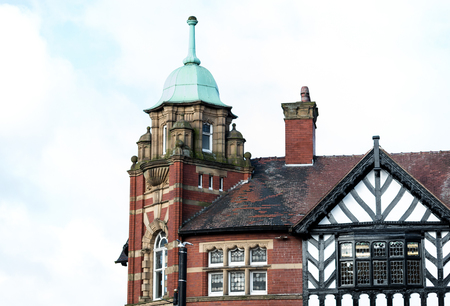 A green covered tower on the end of a red brick building