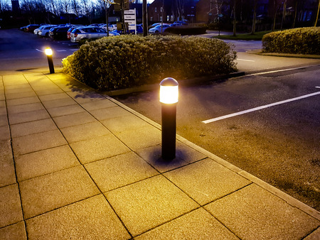 Two small lighting bollards on the edge of a car park