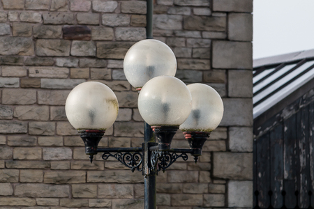 Four spherical opaque lights on a metal pole
