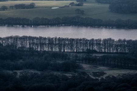 The dark treeline alongside the reservoir