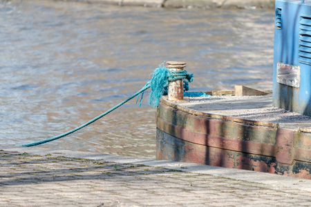 A blue frayed rope moors up the barge to the towpath 写真素材