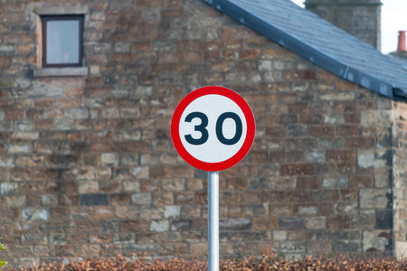 A red and white sign showing the speed limit of 30 mph