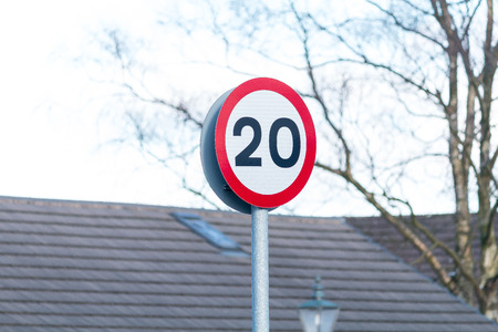 A red and white sign showing the speed limit of 20 mph Stock Photo