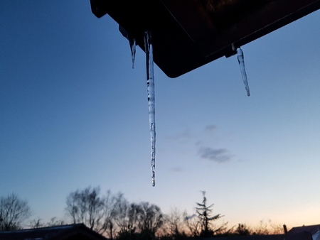 A couple of icicles dangling from the guttering at sunset