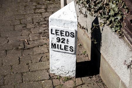 リーズまでの距離を示す白いコンクリートの看板 写真素材