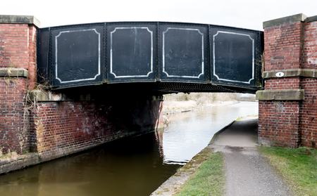 The black bridge over the canal with red brickwork either side