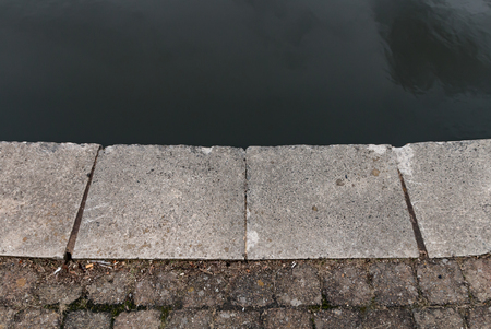 The stone edge to the canal with the paved stoned pathway Stock Photo