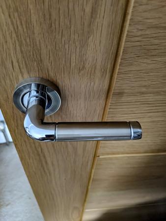 a polished chrome right hand side handle on a light oak door