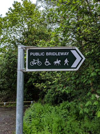 a green and white bridleway sign pointing to the right 스톡 콘텐츠