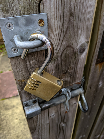 an open brass padlock and bolt on a wooden fence