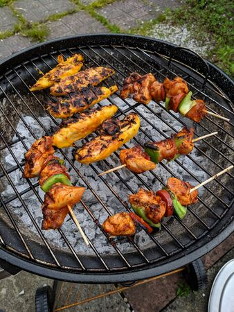 some chicked kebabs cooking on a grill on a bbq