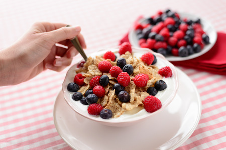 Yogurt and cornflakes with raspberries and blueberries for female diet breakfast