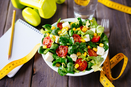 Fitness salad and measuring tabe on rustic wooden table  Mixed greens, tomatos, diet cheese, olive oil and spices for healthy lifestyle concept  photo