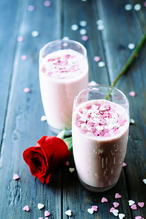 Lovely strawberry milkshakes and red romantic rose with sugar little candy hearts on a rustic wooden table on natural light