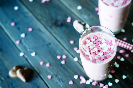 Lovely strawberry milkshake with sugar little candy hearts on a rustic wooden table on natural light