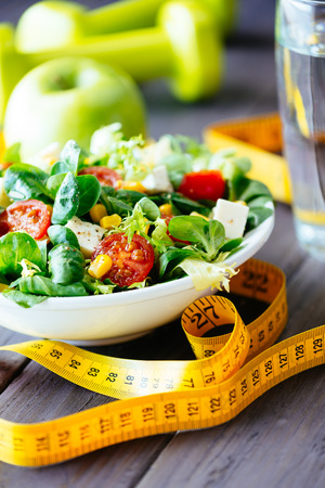 Fitness salad and measuring tape on rustic wooden table  Mixed greens, tomatos, diet cheese, olive oil and spices for healthy lifestyle concept