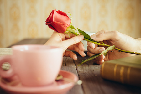 Romantic lovers dating  Love and flirt concept  Man giving rose to woman  Couple on secret dating at coffee shop