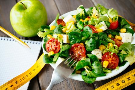 ensalada de verduras: Ensalada de Fitness y cinta de medir en la mesa de madera verdes rústicas mixtas, tomates, queso de dieta, aceite de oliva y especias para el concepto de estilo de vida saludable