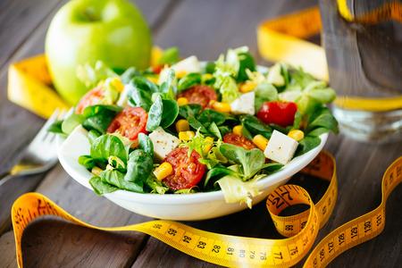 フィットネス サラダ、素朴な木製のテーブル ミックス グリーン、トマト、ダイエット チーズ、オリーブ オイル、健康的なライフ スタイルのコンセプトのためのスパイスのテープを測定