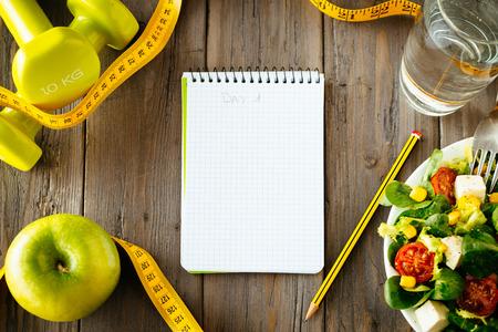 フィットネス: ワークアウトやフィットネス ダイエット コピー スペース日記健康的なライフ スタイル概念のサラダ、アップル、ダンベル、水、素朴な木製のテー