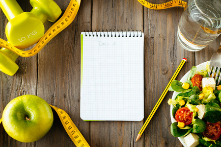 소박한 나무 테이블에 운동 및 피트니스 다이어트 복사 공간 일기 건강 한 생활 양식 개념 샐러드, 사과, 아령, 물, 측정 테이프