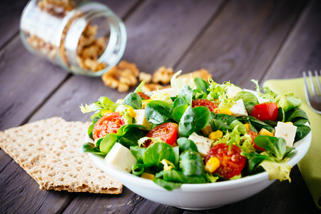 건강 샐러드와 건강 한 라이프 스타일 개념 소박한 나무 테이블 혼합 된 야채, 토마토, 다이어트 치즈, 올리브 오일과 향신료 크래커 다이어트