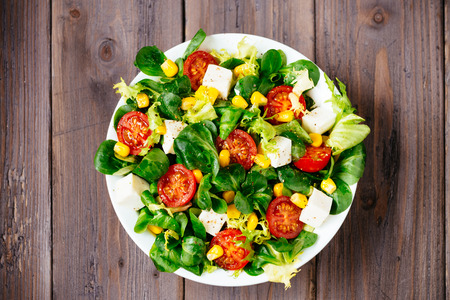 ensalada verde: Dieta saludable ensalada en vista superior de madera r�stica mesa de hojas verdes, tomates, queso de dieta, aceite de oliva y especias para el concepto de estilo de vida saludable Foto de archivo
