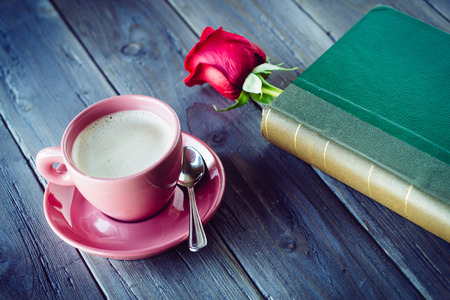 Lovely romantic dating concept with rose, book and coffee cup over rustic wooden table